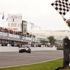 Guido van der Garde takes the flag at the end of the 2014 Goodwood Revival TT Celebration race