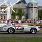 Sir Stirling Moss roars past Goodwood House in a Mercedes-Benz 300 SLR